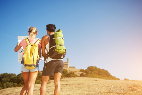 A woman and man with backpacks stop to look at a map on a dry hillside. You cannot see their faces and they are dressed sporty.