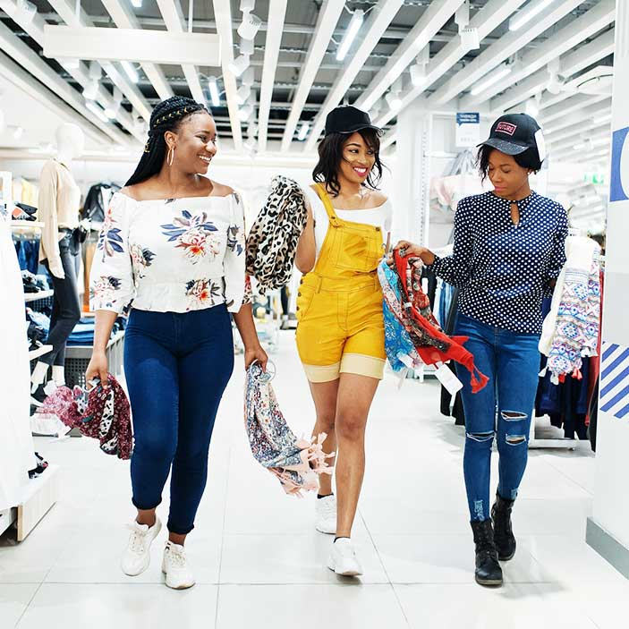 Three female friends shopping for clothes at a store