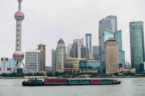 A barge with commercial goods floats on a river channel by downtown Shanghai.