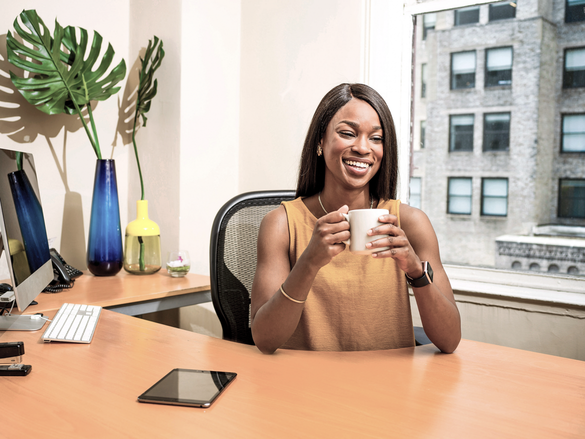 A woman sits at her desk smiling with a cup of coffee in hand. The desk has fake plants and multiple devices on it.