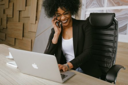 Business woman in a black blazer sitting on a black office chair. She is laughing on the phone while looking at her MacBook.